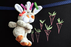 Chalkboard with carrots and toy rabbits Royalty Free Stock Images