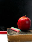 Chalkboard, chalks, apple and old book Royalty Free Stock Photos