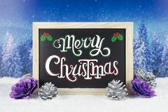 Chalkboard with Christmas decoration on snow and landscape pine tree background, and text `Merry Christmas` written on it.  Stock Image