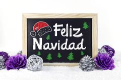 Chalkboard with Christmas decoration with snow white isolated ba. Ckground and text `feliz navidad`, written in spanish, which means `Merry Christmas Stock Photography
