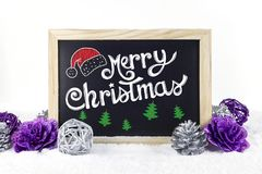 Chalkboard with Christmas decoration on snow white isolated background, and text `Merry Christmas` written on it.  Royalty Free Stock Photo