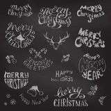 Chalkboard Christmas icons and festive elements. Merry Christmas and Happy New Year lettering. Chalk hand-drawn design elements on blackboard background Royalty Free Stock Photo
