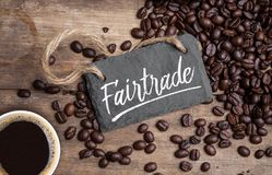Chalkboard with coffee beans and a cup of coffee on natural brown wood stock images
