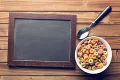 Chalkboard and colorful cereal rings in spoon Royalty Free Stock Images