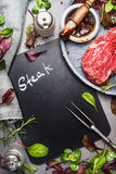Chalkboard cooking background with raw steak, meat fork,fresh seasoning and marinate, top view Stock Photos