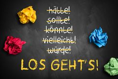 Chalkboard with crumpled paper and stroked words like could and should and `Let`s go`. In German Stock Image