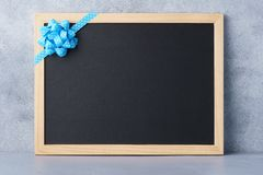 Chalkboard decorated with blue ribbon and bow for advertising. Chalkboard decorated with blue ribbon and bow. Advertising mockup with copy space stock images