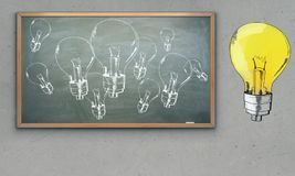 Idea concept. Chalkboard with drawn lamps on concrete wall background. Idea concept Royalty Free Stock Images