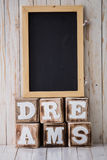 Chalkboard and DREAMS sign made of wooden blocks on wooden backg Royalty Free Stock Photography
