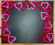 Chalkboard framed by red and pink felt cutout hearts, space Royalty Free Stock Images