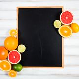 The chalkboard with fresh citrus.  Royalty Free Stock Photo