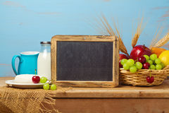 Chalkboard  with fruit basket and milk on wooden table. Jewish holiday Shavuot background with place for text Stock Images