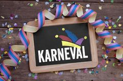 Chalkboard with the german word for carnival - Karneval on wooden background. With streamer and confetti stock photography
