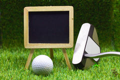 Chalkboard and golf ball on green background Stock Photo