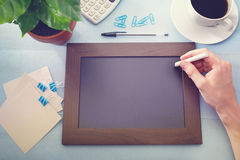 Chalkboard with green plant and office supplies stock photography