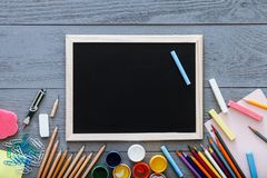 Chalkboard on grey dark desk with colorful pencils, paints, other school supplies for schoolwork, back to school sale concept,. Creative workplace for new stock photo