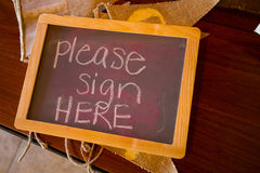 Chalkboard Guestbook Sign. Please sign here written in chalk on a guestbook table sign royalty free stock photo