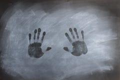 Chalkboard Hand Prints. Hand prints on a smudged black chalkboard royalty free stock photo