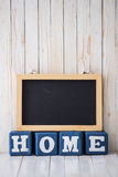 Chalkboard and HOME sign made of wooden blocks on wooden backgro Royalty Free Stock Image