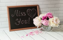 Chalkboard with inscription Miss You and peonies Royalty Free Stock Photography