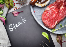 Chalkboard with inscription Steak, raw beef steak and ingredients for grill or BBQ on rustic kitchen table, top view Stock Images