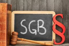 Chalkboard law book and paragraph as law concept. German abbreviation SGB for Sozialgesetzbuch Sozial Book of law on chalkboard and paragraph as law concept stock photography