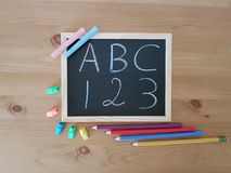 Chalkboard with writing utensils stock images