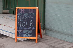 Chalkboard menu inviting folks in for happy hour. Large chalkboard menu set outside restaurant, inviting folks in for specialty drinks and happy hour prices Royalty Free Stock Photos