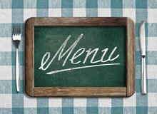 Chalkboard with menu text on picnic tablecloth Royalty Free Stock Image