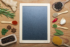 Chalkboard menu on a wooden background with spices Royalty Free Stock Images