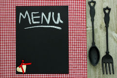 Chalkboard menu znak na czerwonym w kratkę tablecloth z obsady żelaza rozwidleniem i łyżką fotografia stock