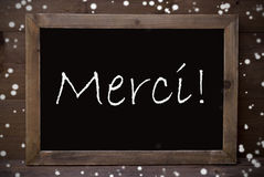Chalkboard With Merci Means Thank You, Snowflakes Stock Photos
