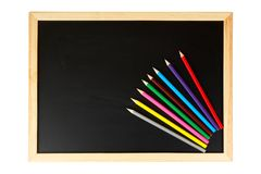 Chalkboard and multicolored pencils. A empty black chalkboard with multicolored pencils. Isolated on white background Royalty Free Stock Photo