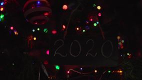 2020 lettering chalkboard hanging on a branch is Christmas tree. Chalkboard with number 2020 title on it hanging on branch is Christmas tree among glass balls stock footage