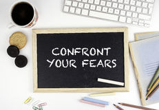 Chalkboard on office desk with text: Confront Your Fears.  stock photos