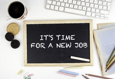 Chalkboard on office desk with text: IT'S TIME FOR A NEW JOB Stock Images
