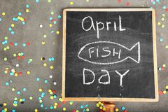 Chalkboard with phrase. `April fish day` and confetti on grey background Stock Photo