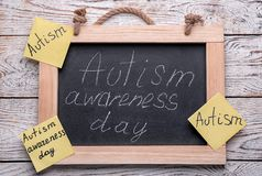 Chalkboard with phrase. `Autism awareness day` on wooden background Stock Photo