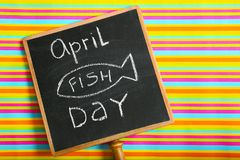 Chalkboard with phrase. `April fish day` on color background Royalty Free Stock Images