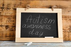 Chalkboard with phrase. `Autism awareness day` on table Stock Image