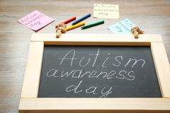 Chalkboard with phrase. `Autism awareness day` on wooden background Royalty Free Stock Photos