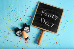 Chalkboard with phrase. `Fool`s day` and funny glasses on color background. 1st April celebration Royalty Free Stock Image