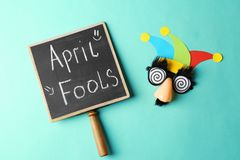 Chalkboard with phrase. `Fool`s day` and funny glasses on color background. 1st April celebration Royalty Free Stock Photos