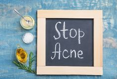 Chalkboard with phrase. `Stop acne` and ingredients for homemade problem skin remedy on wooden background Stock Images