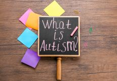 Chalkboard with phrase. `What is autism?` on wooden background Stock Photo
