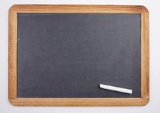 Chalkboard with piece of chalk Stock Photos