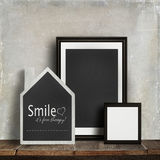Chalkboard with quote and frames on table Royalty Free Stock Photo