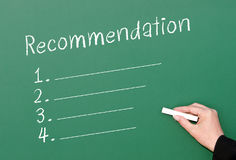 Chalkboard recommendation checklist. Green chalkboard with a blank list of numbered recommendations and a hand holding chalk ready to write Royalty Free Stock Image