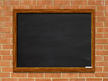 Chalkboard on Red Brick Wall. Chalkboard with wooden frame on red brick wall stock photography