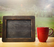 Chalkboard with red mug over country landscape Royalty Free Stock Photo